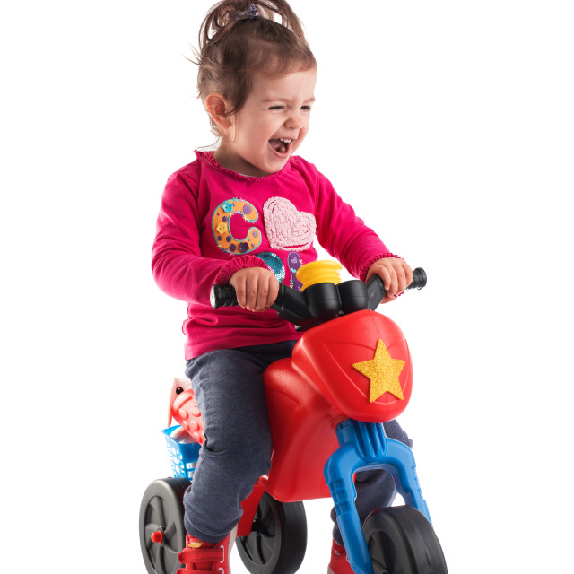 """""""Little girl riding a motorcycle isolated on white background"""" stock image"""