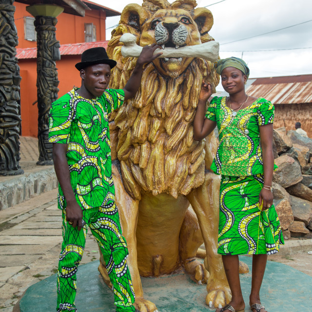 """Benin, West Africa, Savalou, couple pausing in front of a lion statue in the..."" stock image"