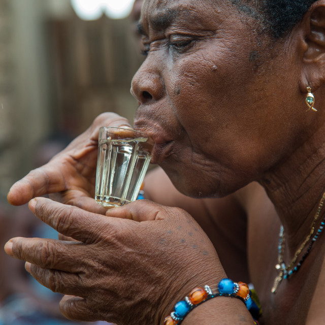 """Benin, West Africa, Bopa, woman drinking alcohol during a voodoo ceremony"" stock image"
