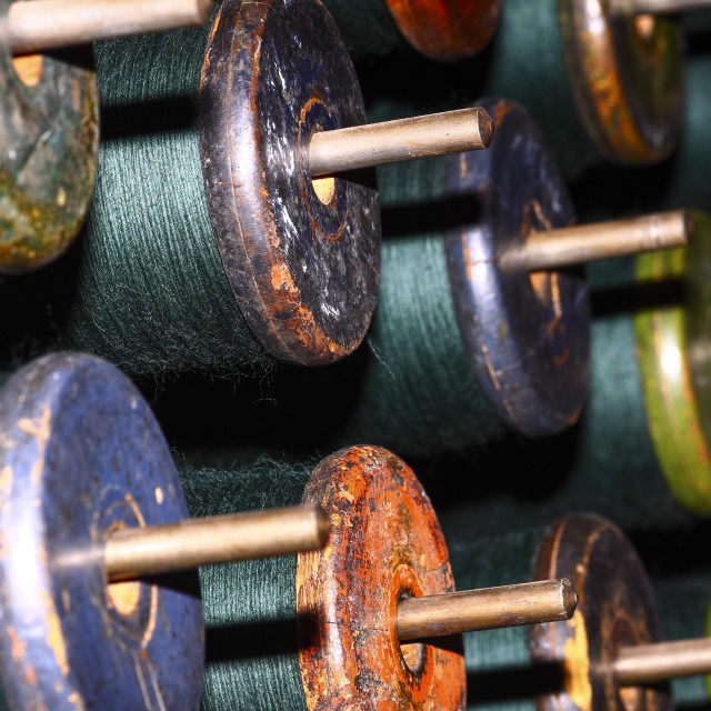 """Close up green cotton bobbins loaded on to a weaving loom"" stock image"
