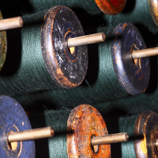 """""""Close up green cotton bobbins loaded on to a weaving loom"""" stock image"""