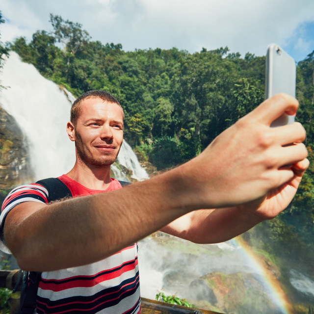 """""""Tourist taking a selfie against waterfall"""" stock image"""