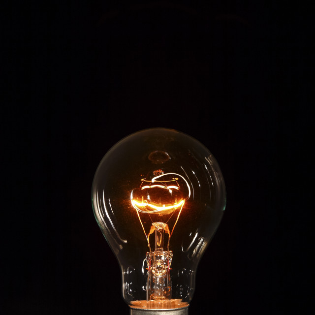 """Clear lightbulb glowing isolated on a black background"" stock image"