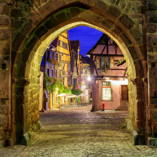 """""""View of Riquewihr, Alsace, France, through city wall gate at night"""" stock image"""