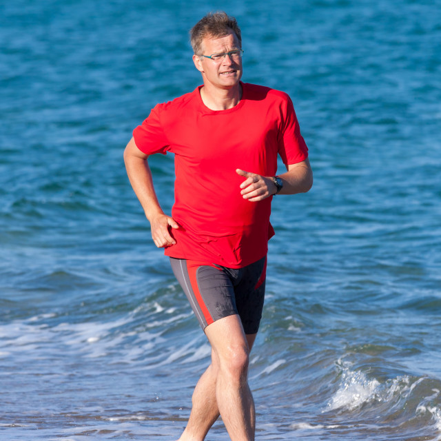 """""""Young man running on the beach in Costa Brava, Spain"""" stock image"""