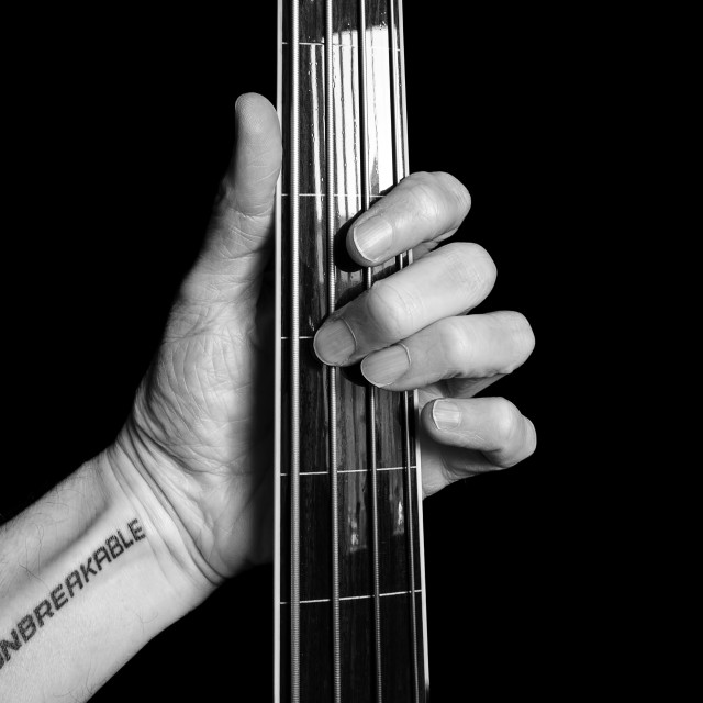 """Tattooed guitarist's hand arm and bass guitar,"" stock image"