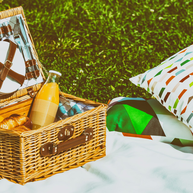 """Picnic Basket Food On White Blanket With Pillows In Summer"" stock image"