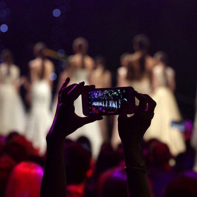 """""""Fashion show runway taking picture with phone"""" stock image"""