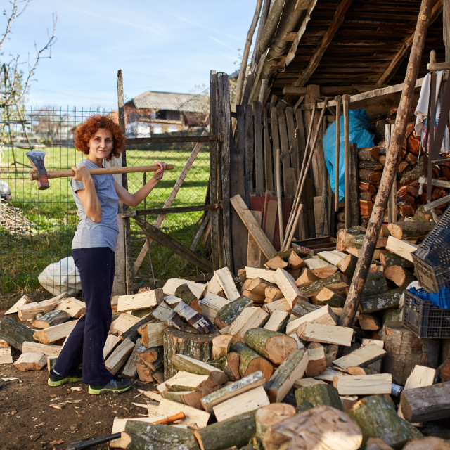 """Woman splitting wood"" stock image"