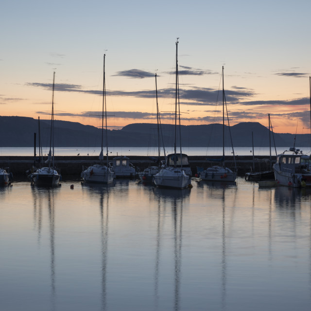 """Yachts moored in The Cobb with Jurassic Coast and Golden Cap at sunrise, Lyme..."" stock image"