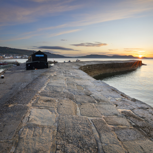 """The Cobb with the cliffs of Jurassic Coast at sunrise, Lyme Regis, Dorset,..."" stock image"