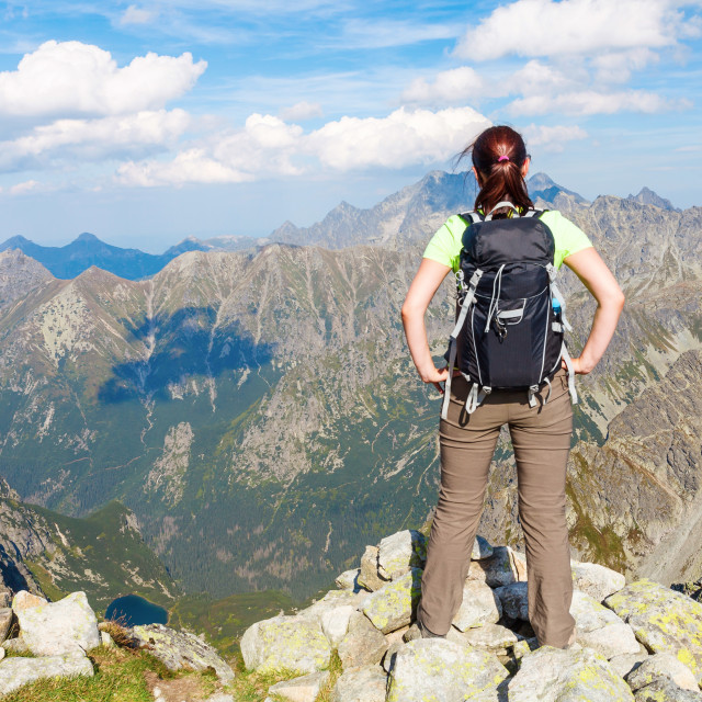 """Woman with backpack standing on the edge, looking at mountains"" stock image"