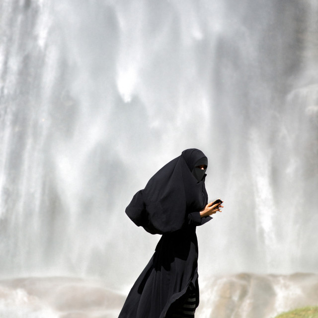 """Islamic woman dressed in a full burka standing on green grass using a smartphone, side view with copyspace above"" stock image"