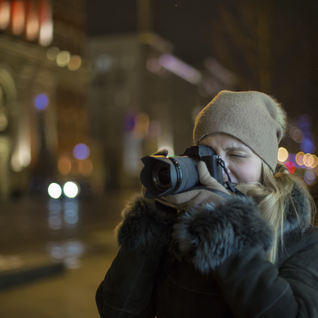 """""""Woman photographer makes photos in the night city"""" stock image"""