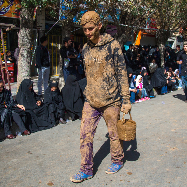 """Iranian Shiite Muslim Man Covered In Mud With A Bucket During Ashura Day,..."" stock image"