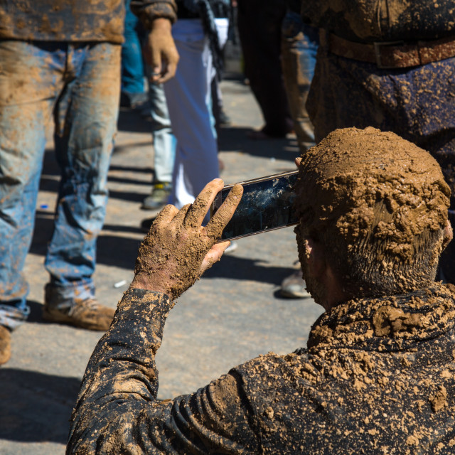"""Iranian Shiite Muslim Man Covered In Mud Taking Pictures With A Mobile Phone..."" stock image"