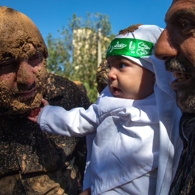 """Iranian Shiite Baby Touching The Beard Of A Man Covered In Mud During Ashura..."" stock image"