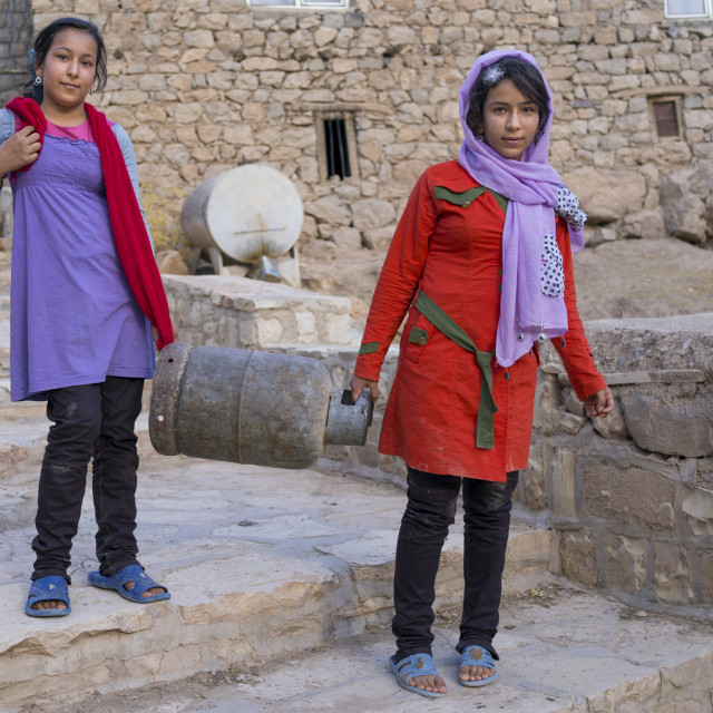 """Girls Carrying A Gas Bottle In The Old Kurdish Village Of Palangan, Iran"" stock image"