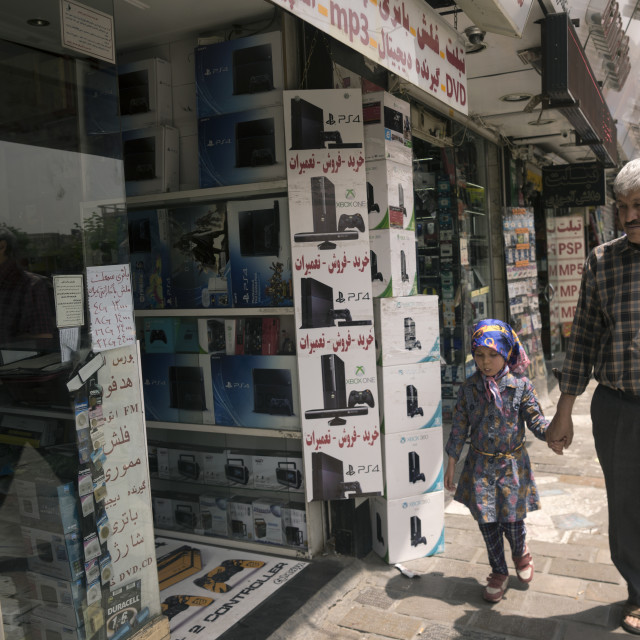 """""""Father and daughter passing in front of an electronics shops, Shemiranat..."""" stock image"""