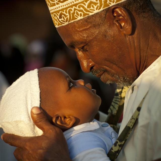 """""""Father Carrying Small Baby With Coaled Eyelids During Maulidi, Lamu, Kenya"""" stock image"""