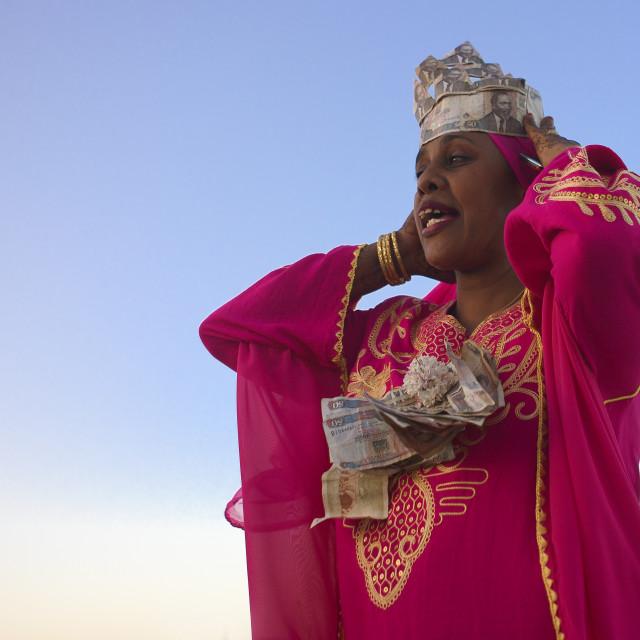 """Woman Wearing Banknotes Arranging Herself During Maulidi Festival, Lamu, Kenya"" stock image"