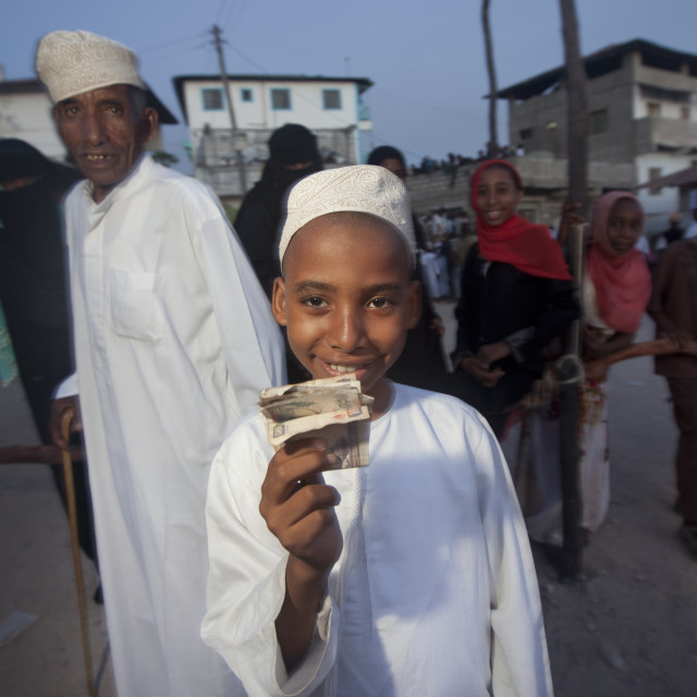 """Kofia Headed Young Boy Brandishing His Reward: Banknote In Lamu, Kenya"" stock image"