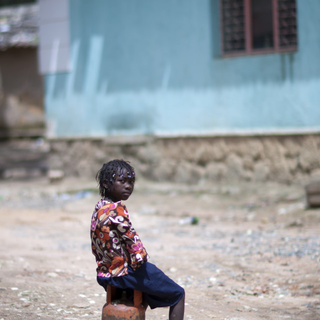 """Girl Sitting On A Bottle Of Gas, Huambo, Angola"" stock image"