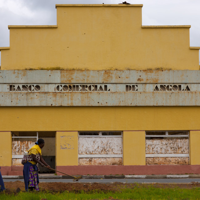 """""""Women Ploughing In Front Of An Old Bank In Ruins, Vila Nova, Angola"""" stock image"""