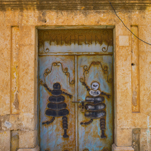 """Old Italian Colonial Shop With Michelin Bibendum, Ptolemais, Libya"" stock image"