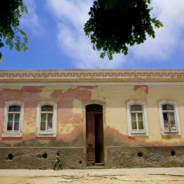 """Girl Passing By A Colonial Building In Namibe Town, Angola"" stock image"