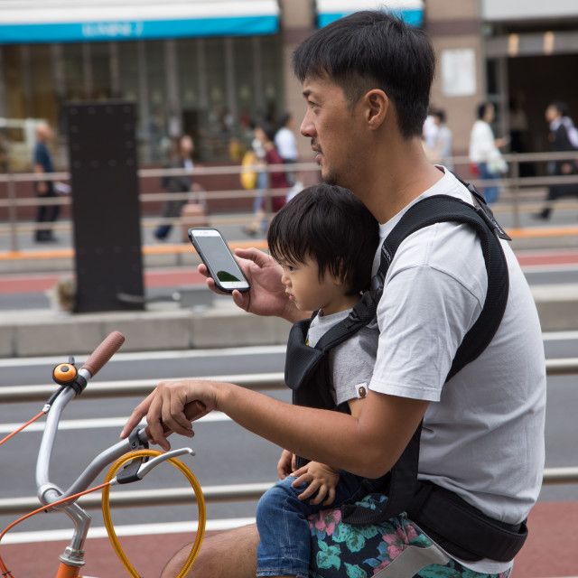 """""""Father looking at his smart phone while riding a bicycle with his child,..."""" stock image"""