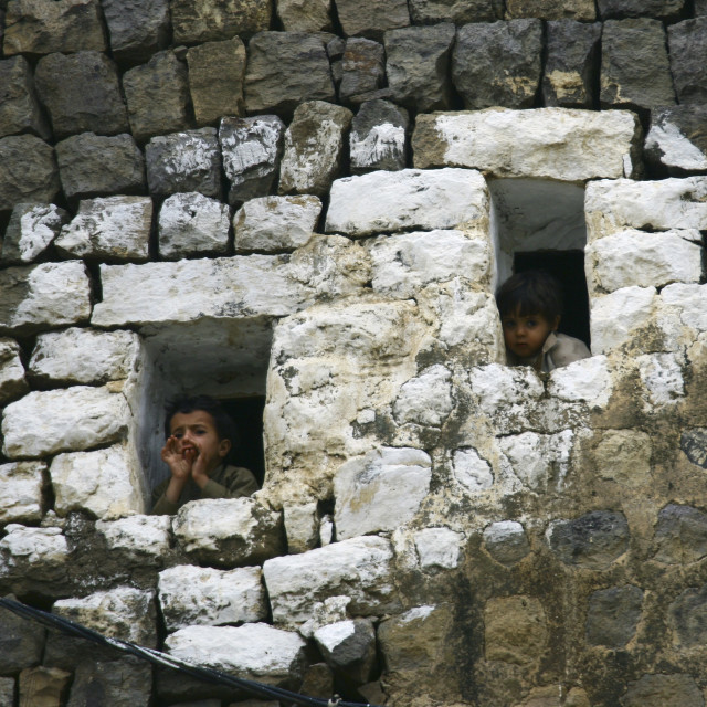 """Two Kids Looking Outside From The Small Windows Of A House, Al Hajjara, Yemen"" stock image"