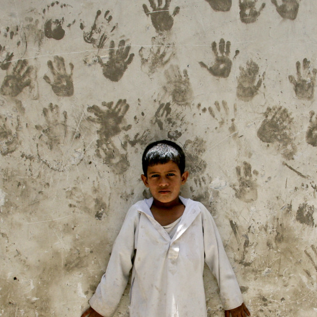 """Child In Front Of A Wall Covered With Handprints To Protect From The Evil..."" stock image"