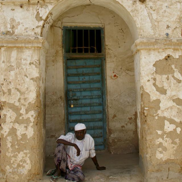 """Man With White Taqiyah Sitting On The Ground And Looking At Camera, Tarim, Yemen"" stock image"
