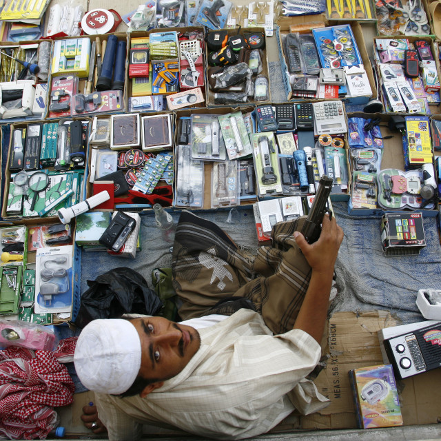 """""""Seller Holding A Gun And Sitting Among The Items For Sale, Tarim Market, Yemen"""" stock image"""