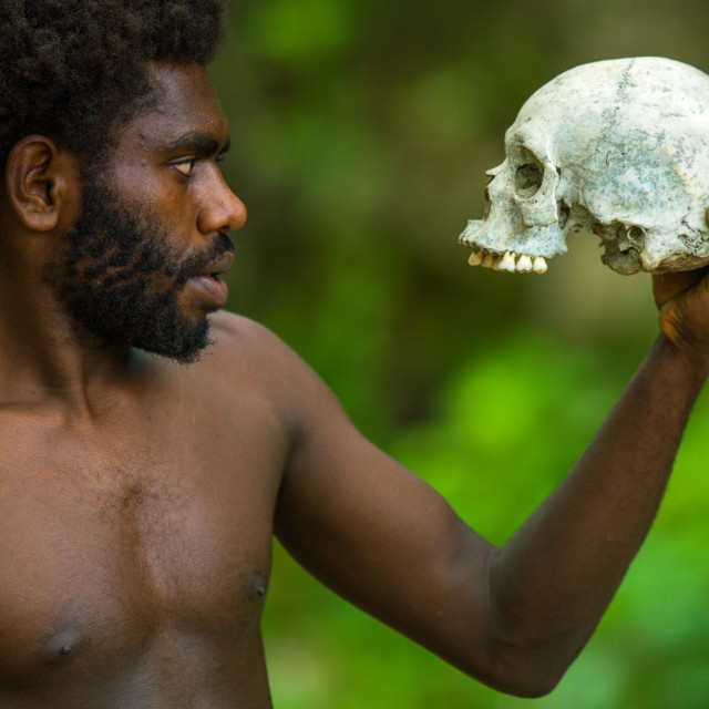 """""""Man holding a human skull in Amelbati cannibal site, Malampa Province,..."""" stock image"""