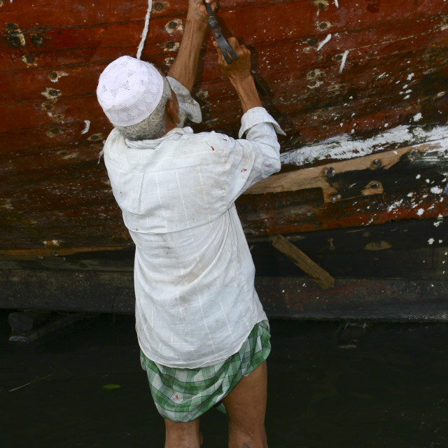 """Man Working On The Impermeability Of A Dhow, Al Hodeidah Harbour, Yemen"" stock image"