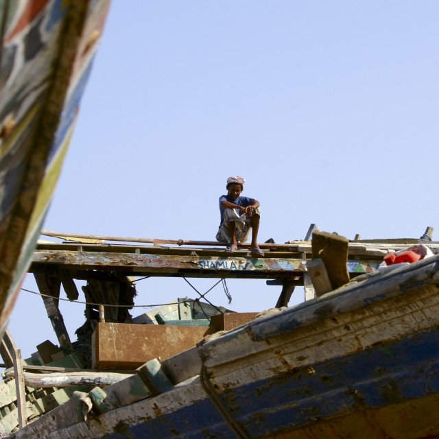 """Young Man Sitting On The Top Of A Dhow, Al Hodeidah Harbour, Yemen"" stock image"