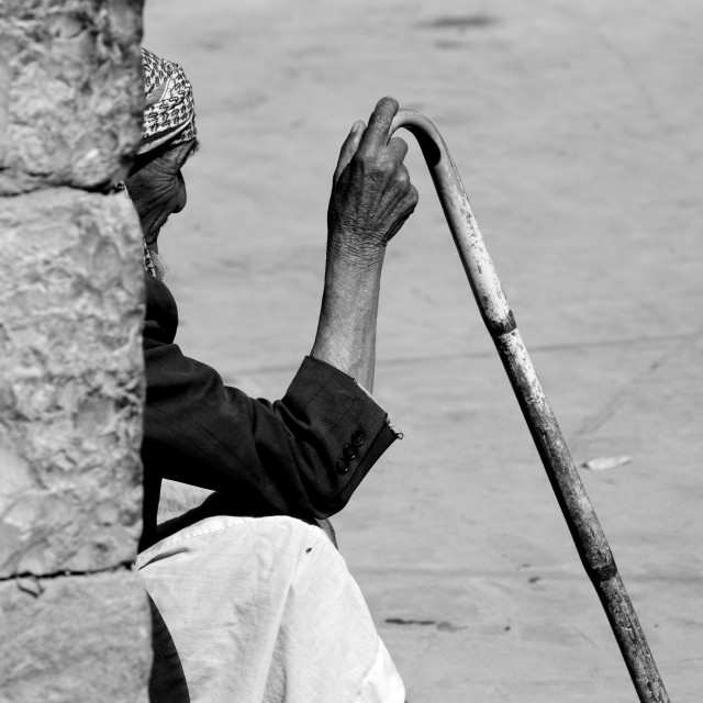 """Old Man Sitting Against A Wall And Holding A Cane In Shibam, Yemen"" stock image"