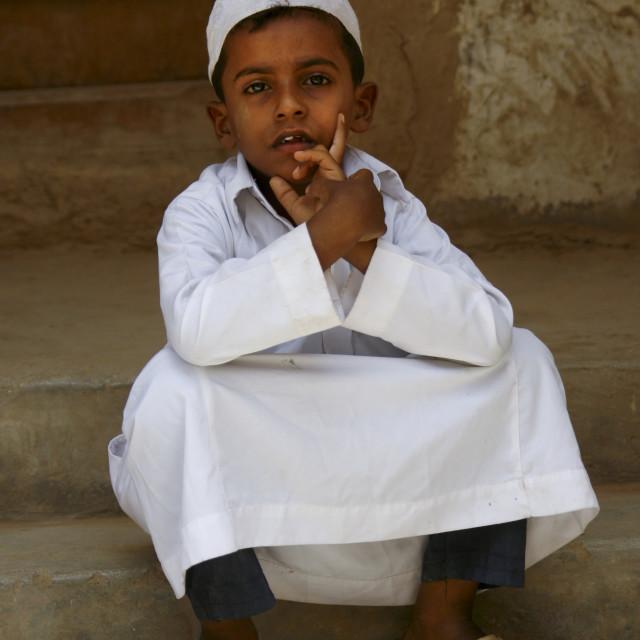 """""""Yemeni Boy With White Taqiyah Sitting On Doorstep, Tarim, Yemen"""" stock image"""
