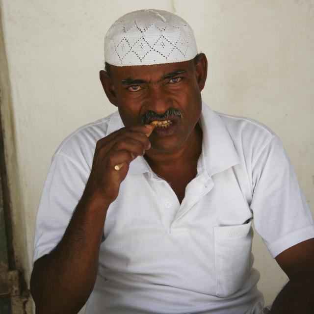 """""""Yemenni Man With White Taqiyah Chewing A Toothbrush Stick, Tarim, Yemen"""" stock image"""