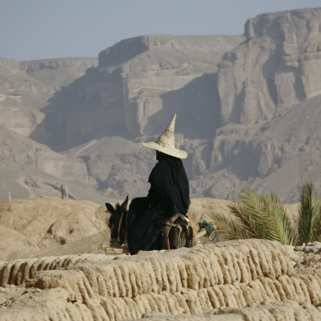 """""""Woman Wearing A Tall Cone Hat And Riding On A Donkey In Rocky Land,..."""" stock image"""