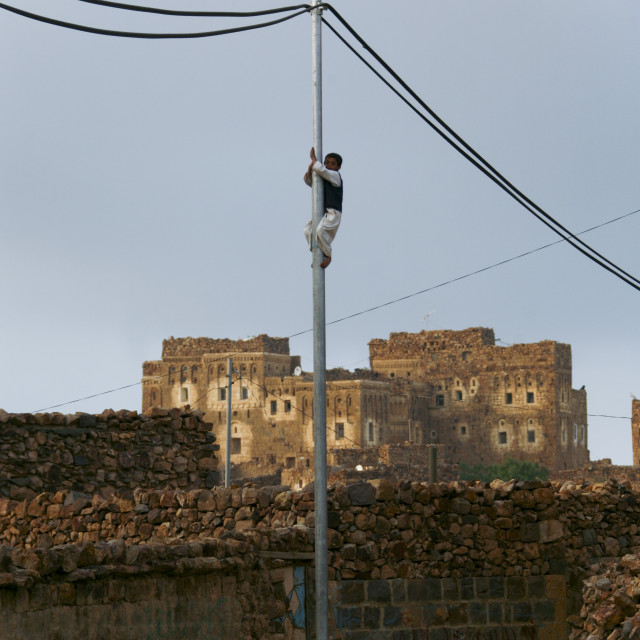 """Boy Climbing On A Telephone Pole, Shahara, Yemen"" stock image"