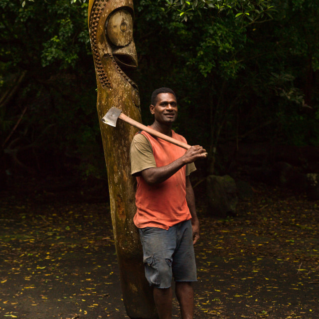 """""""Ni-Vanuatu man with an axe in front of a slit gong drum in the jungle, Ambrym..."""" stock image"""