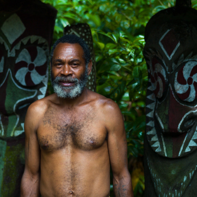"""Portrait of a leader in front of slit drums, Ambrym island, Olal, Vanuatu"" stock image"