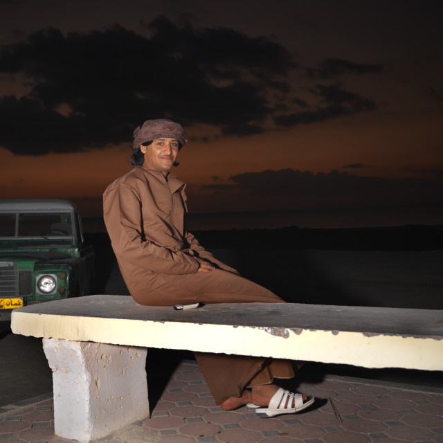 """Bedouin Man Sitting On The Bench, Masirah Island, Oman"" stock image"