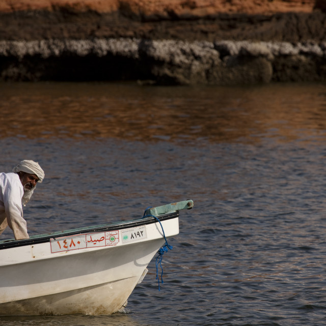 """Fisherman Bending Down On The Boat, Sur, Oman"" stock image"
