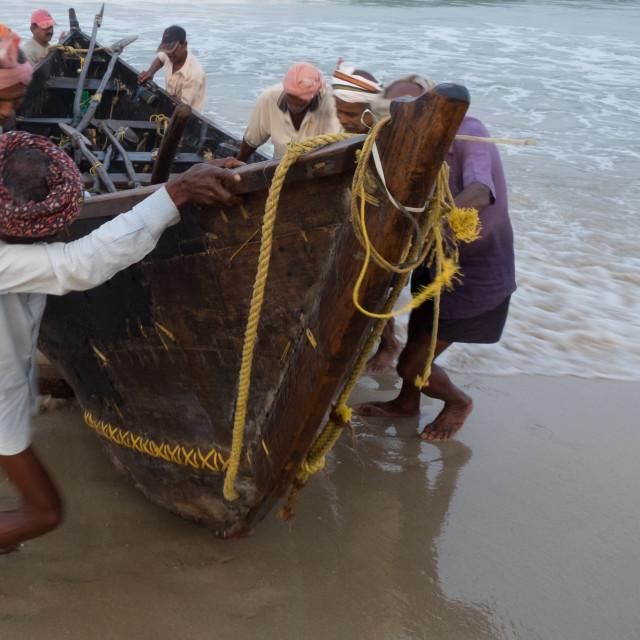 """""""Fishermen beaching their boat - India"""" stock image"""