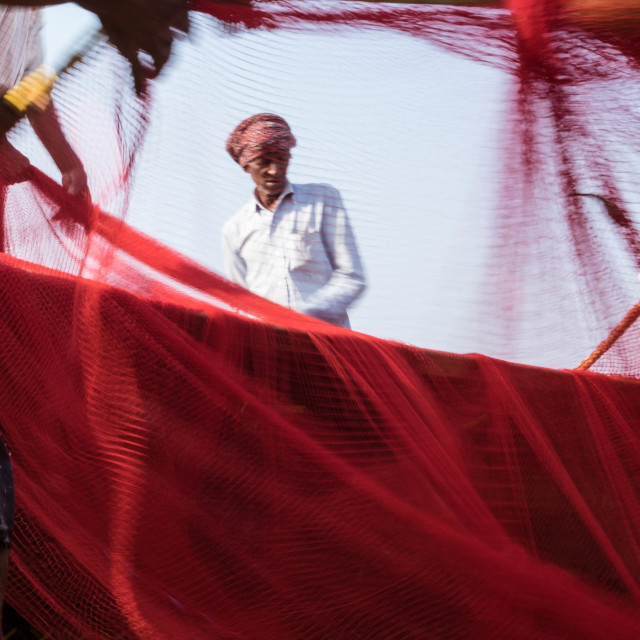 """""""Cleaning and coiling their nets - fishermen in India"""" stock image"""