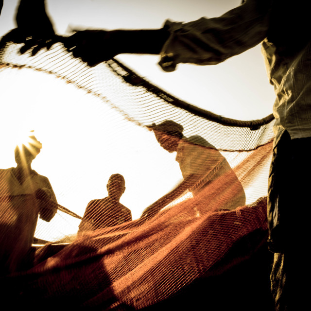 """""""Sunstruck fishermen cleaning and coiling their nets - Indiia"""" stock image"""